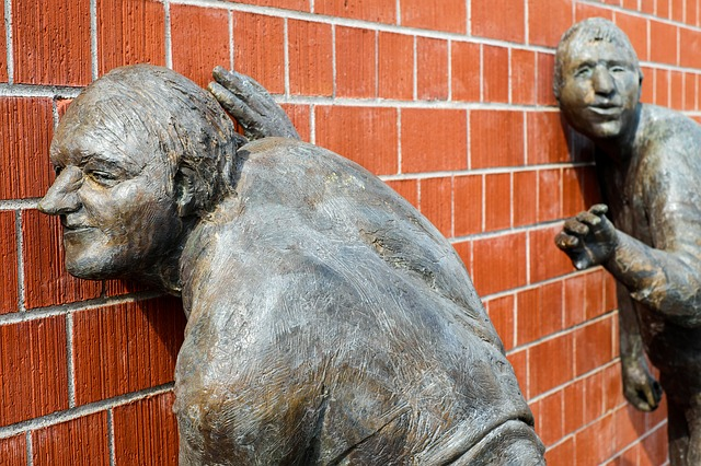 Sculpture of two males with their ears against a brick wall, actively listening.