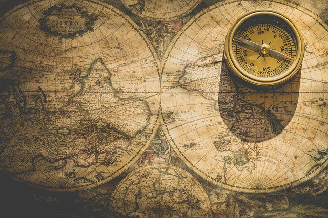 Antique map of the world with a compass on the right hand side of the picture.