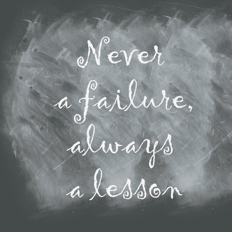 "A black chalkboard with the words, ""Never a failure, always a lesson"" in white, cursive writing."