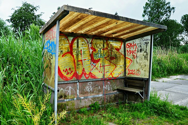Abandoned bus stop with colorful graffiti on its walls.