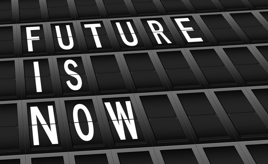"""Future Is Now"" sign, white block letters on a black background."