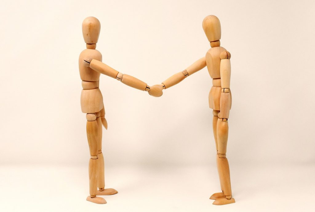 Two wooden stick figures shaking hands.