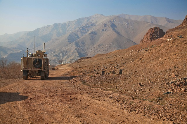 Dirt road and mountainous terrain with a Humvee.