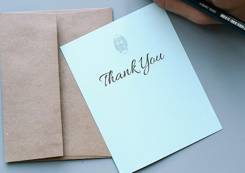 "A pastel green ""Thank You"" note resting on top of a brown envelope."