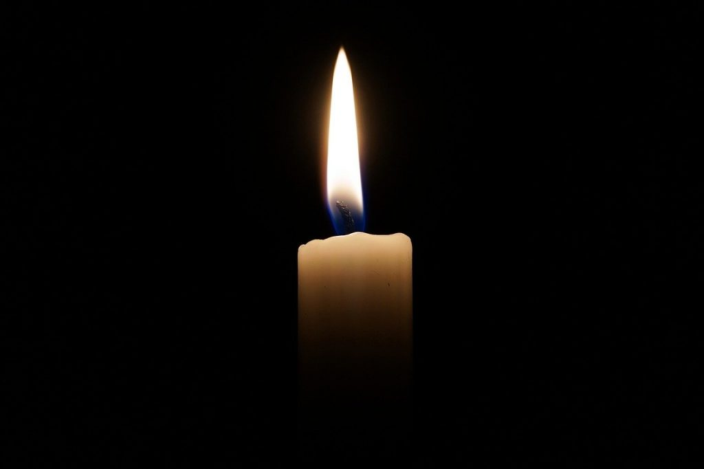 A lit candle with a black background.