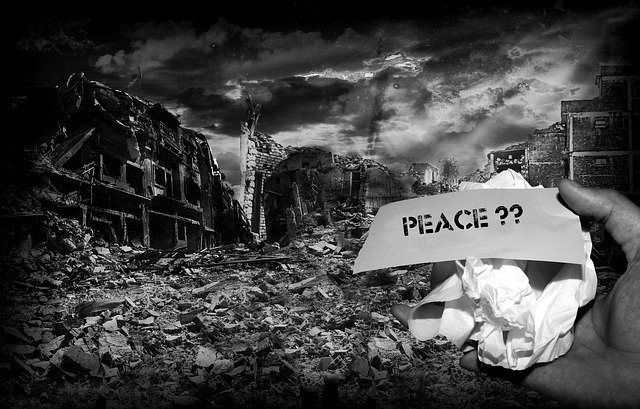 "Black and white image showing total destruction of a city with a hand holding a ""Peace??"" sign."