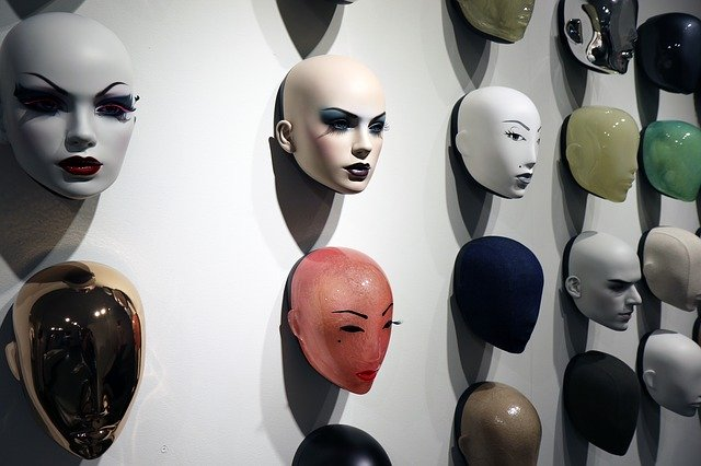A display of mannequin heads of various colors on a wall.