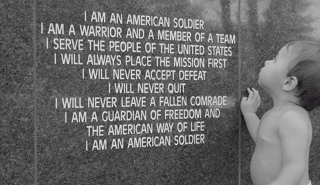 Soldier's Creed with a baby standing next to it.