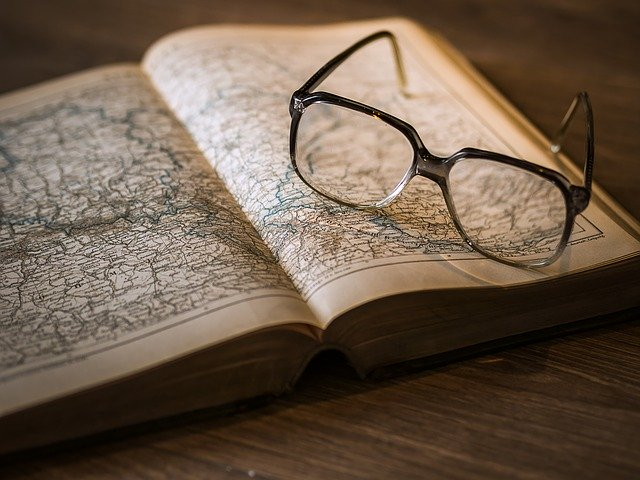 An open book with an ancient map and eyeglasses sitting on top of the right page.
