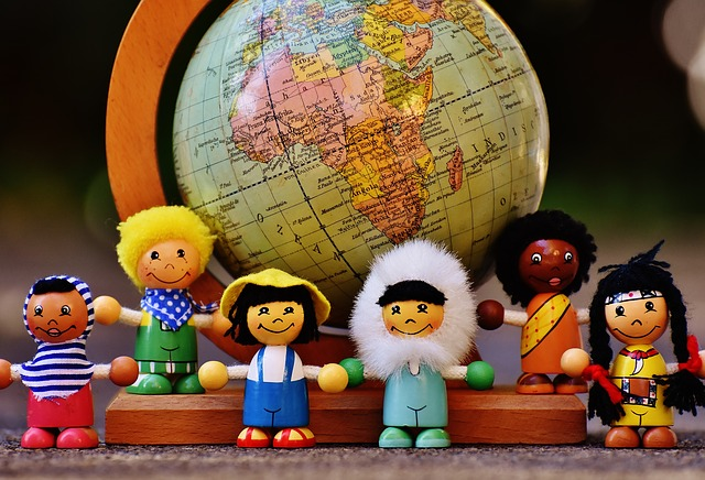 Wooden dolls dressed of different nationalities standing in front of a globe.