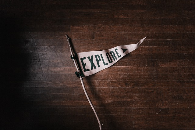 """""""Explore"""" white flag with wooden background."""