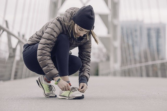A woman hunched over trying her sneakers.