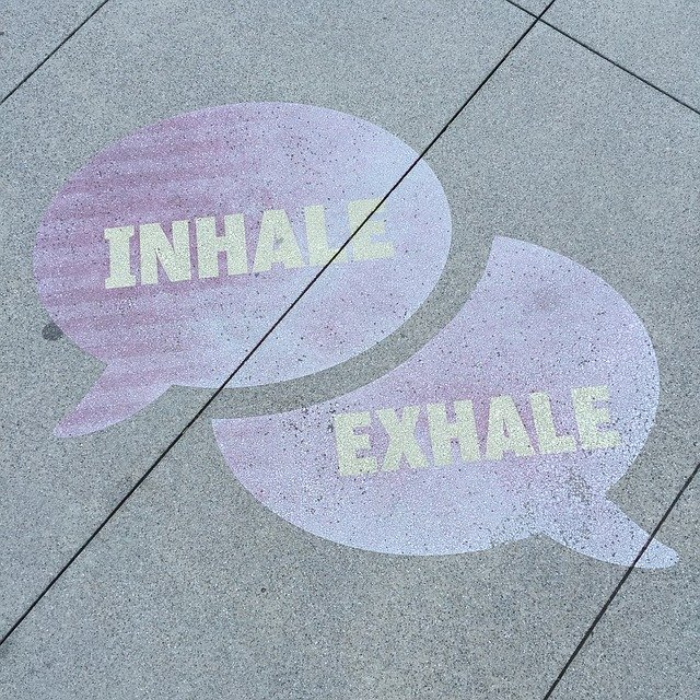 """Inhale"" and ""exhale"" in speech bubbles on sidewalk."