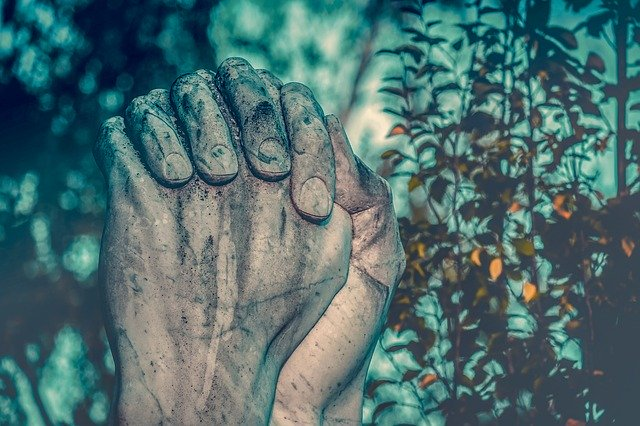 Hands sculpted in stone as if to pray.