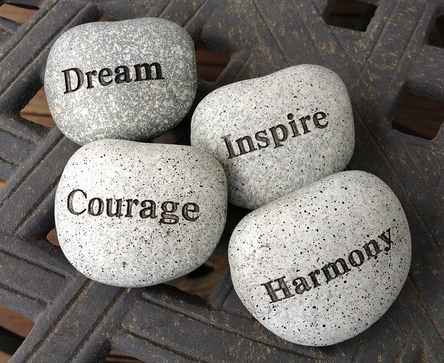 "Stones with inspirational words carved on them (""Dream,"" ""Courage,"" ""Inspire,"" and ""Harmony"")."